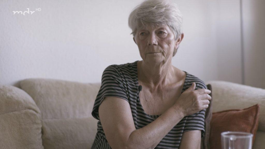 Weiße Rentnerin sitzt auf ihrem Sofa